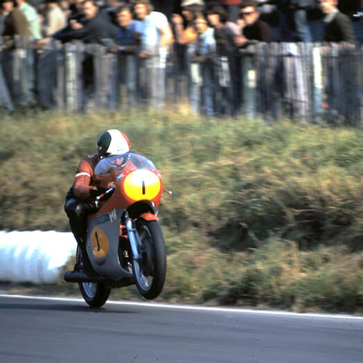 Giacomo-Agostini riding MV-Agusta-ITA doing a wheelie